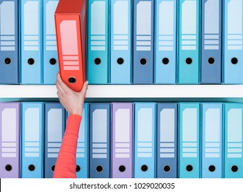Office worker finding a folder in the archive: database, administration and file management concept