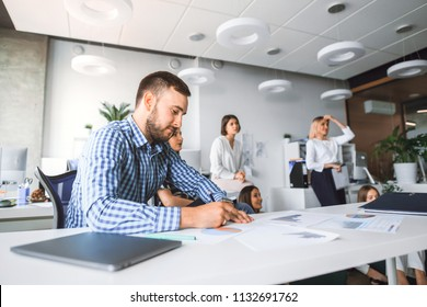 Office worker in the foreground sitting at the table making records in documents on the background of business colleagues