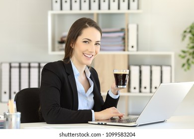 Office worker holding a coffee cup looking at camera at workplace