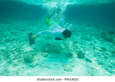 Office worker with keyboard swimming underwater in formal clothes with red tie