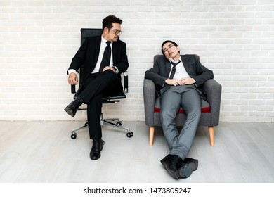 Office worker looking at friend sleeping on chair, Concept of fatigue at work
