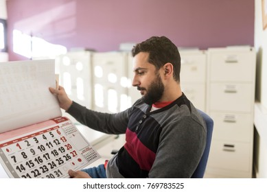 Office worker looking his work calendar for preparing year of work and vacations