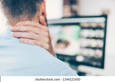 Office worker with neck and back pain from sitting at desk all day