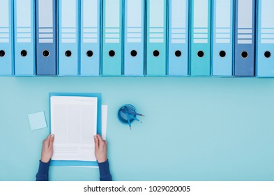 Office worker reading paperwork and archive binders, files database and management concept, top view