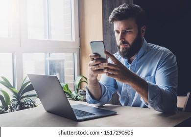 Employé de bureau se reposant, jouant à des jeux en ligne sur smartphone. Un homme télécharge des applications intéressantes sur son appareil mobile. Travailleur indépendant à domicile à la recherche d'instructions sur son travail. E-mail de vérification pour adultes masculins
