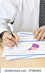 Office worker reviewing generic presentation charts and reports