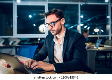 Office worker sending emails from computer. Good looking bearded businessman with serious face expression working late at night typing on laptop with screen light shining on his face.