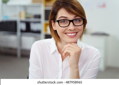 Office worker with short brown hair smiles at camera while her chin rests on one hand