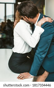 An office worker sits on a desk while a colleague kisses her neck. Passionate affair in the office workplace concept. High quality photo.