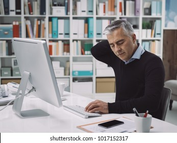 Office worker sitting at desk and having neck pain, he is massaging his neck: stress and overwork concept