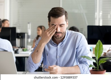 Office worker sitting at desk taking off glasses rubbing massaging eye tired of working at computer having blurry vision problem and dry eyes after long use of laptop, suffering from eyestrain at work