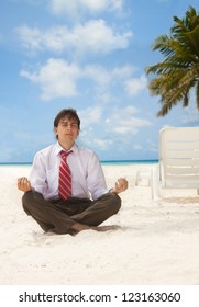 Office worker sitting on the beach an meditating