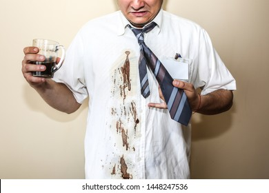Office worker spills coffee on white shirt. Occupational burnout. Unhappy manager with mug in hands. Stressful job. Desperate man.