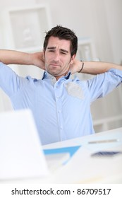 Office worker stretching arms at work