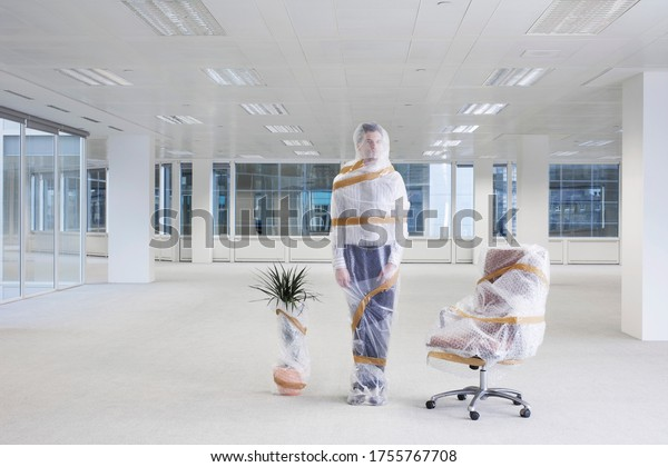 Office worker swivel chair and potted plant covered with bubble wrap and tape in empty office space