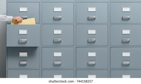 Office worker taking a file from a filing cabinet drawer, business and administration concept
