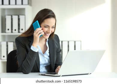 Office worker talking on a phone call and checking data in a laptop
