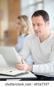 Office worker in the office using electronic tab