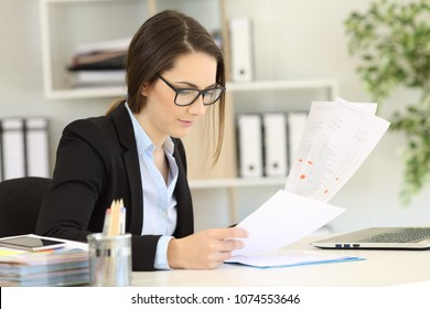 Office worker wearing eyeglasses checking paper documents