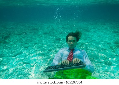 Office worker wearing formal clothes with keyboard underwater