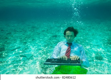 Office worker wearing tie and white shirt with keyboard underwater