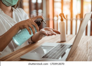 Office worker working from home during coronavirus outbreak cleaning her hands with sanitizer gel and wearing protective mask. Coronavirus, covid-19, Work from home (WFH), Social distancing concept.