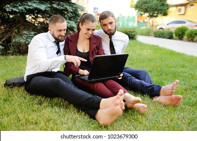 office workers in business clothes sitting barefoot on the grass. Lunch break, yoga, relaxation