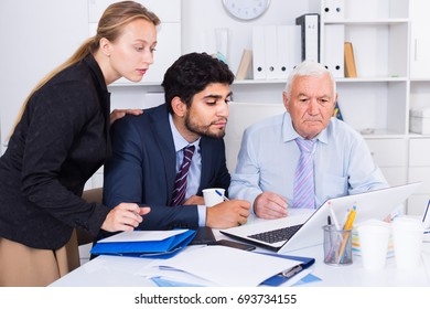 Office workers are demonstrating reports on laptop to mature boss in the office.