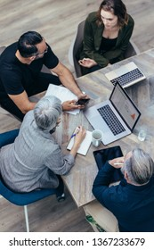 Office workers gather around a table to do research and implement new ideas. High angle view of business people discussing new plan in a meeting.