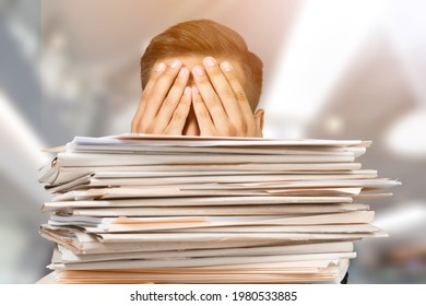 Office workers holding and writing documents on a desk with a stack of business overload paper.