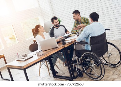 Office workers and man in a wheelchair are making a conversation in bright office. They are showing a teamwork.
