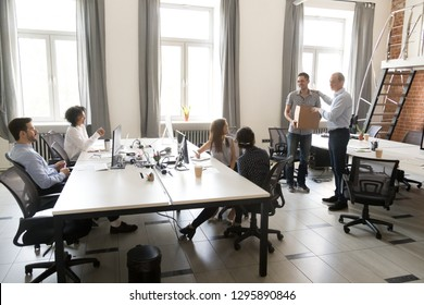 Office workers sitting on their places looking at boss ceo introduce a new employee to colleagues. Millennial man holds box has first workday in company getting vacancy feels satisfied and happy