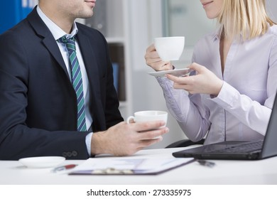 Office workers sitting at the table and drinking coffee