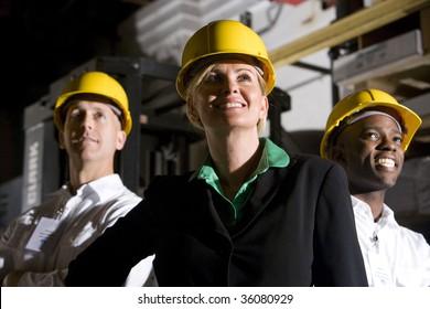Office workers in storage warehouse wearing hard hats