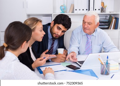 Office workers are writing financial reports and discussing with mature boss in the office.