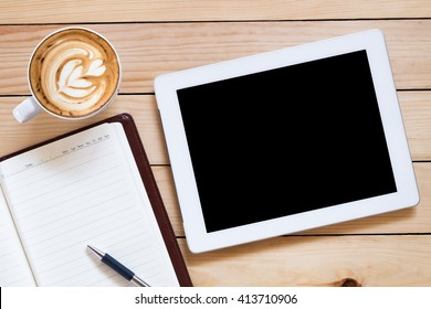 Office workplace with blank screen tablet, notebook, pen and coffee cup on rustic wood table.Top view.Office supplies and gadgets on workplace.Working desk table concept.Flat lay image.