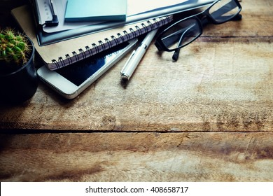 Office workplace with digital smartphone pen notepad and green plant. Creative studio concept