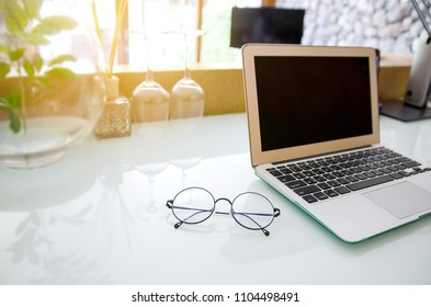 Office workplace with laptop and eye glasses on high gloss office desk table.