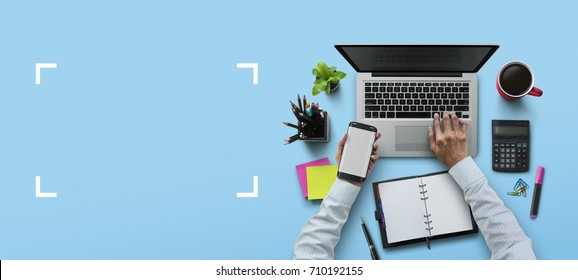 Office workplace with laptop, notebook, hand, office supplies, on blue background. Solution, business planning, financial analysis, accounting, start up or working flat lay top view concept.