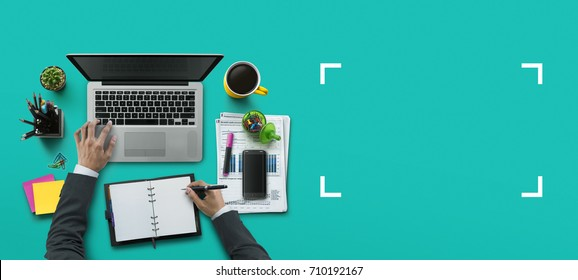 Office workplace with laptop, notebook, hand, office supplies, on turquoise background. Solution, business planning, financial analysis, accounting, start up or working flat lay top view concept.