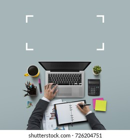 Office workplace with laptop, notebook, hand, office supplies, on gray background. Solution, business planning, financial analysis, accounting, start up or working flat lay top view concept.