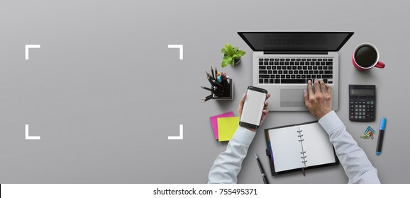 Office workplace with laptop, notebook, hand, office supplies, on gray background. Solution, business planning, financial analysis or working flat lay top view concept.