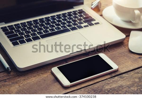 Office workplace with laptop notepad pencil coffee of cup and smartphone on wood table.vintage effect