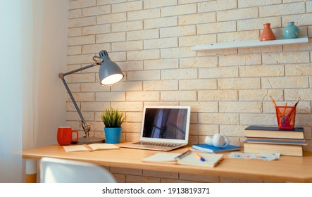 Office workplace with laptop on wooden table.
