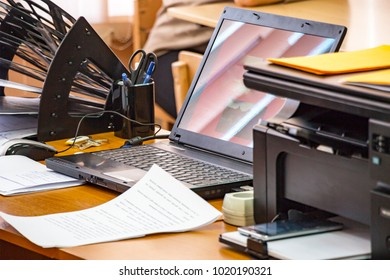 Office workplace with laptop, printer, stand for papers and business papers on the table