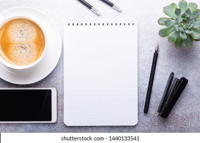 Office workplace with note pad, cup of coffee, smartphone and stationery on gray stone background Top view Copy space