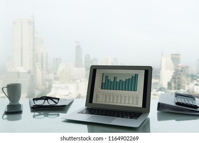 office  workplace with notebook laptop, financial report, calculator on work desk in office with city view.