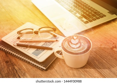 Office workplace with notebook on wood table and hot coffe