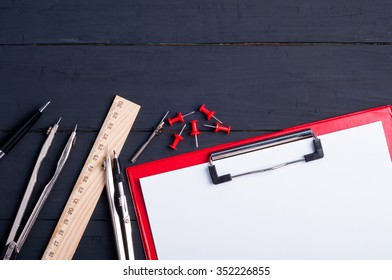 Office workplace. White blank paper, pen, pencil, ruler, divider compass on dark wooden background. Engineering tools. Copy space. Top view