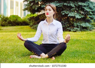 Office yoga. Business lady in lotus pose sits on green grass. Recreation of office staff. Healthy lifestyle.